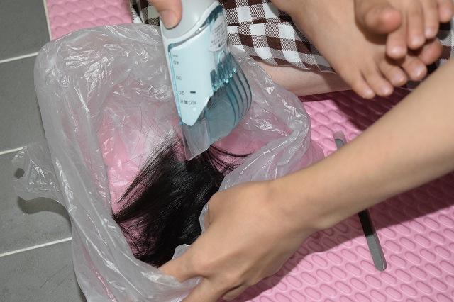 3歳児散髪中 切った髪の毛は袋に入れる